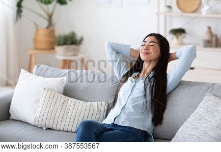 Home Comfort. Young Asian Lady Relaxing On Cozy Sofa In Living Room, Leaning Back On Couch With Clos