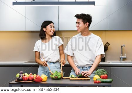Loving Asian Couple Cooking Healthy Food Making Vegetable Salad Standing In Kitchen At Home. Japanes