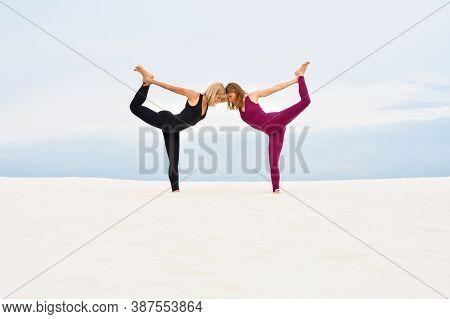 Two Beautiful Young Women Performing Steamy Yoga On The Beach, Nataradzhasana