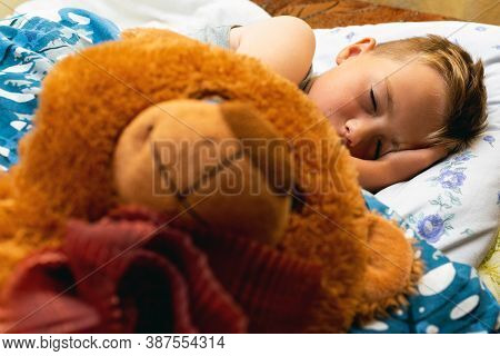 Photo Of Little Cute Schoolboy Sleeping With Big Brown Teddy Ber In Bed. Eyes Are Closed.