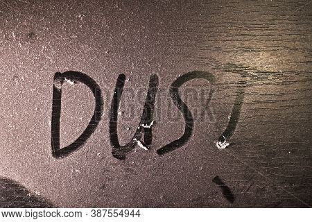 Thick layer of dust on a shelf with word dust written in it