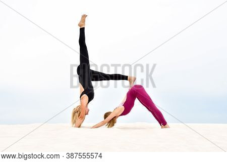 Two Beautiful Young Women Practice Steamy Yoga On The Beach