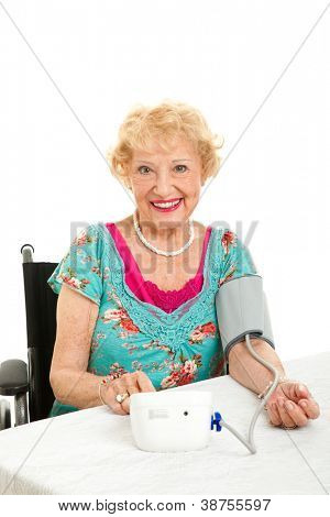 Senior woman taking he own blood pressure at home.  Isolated on white background.