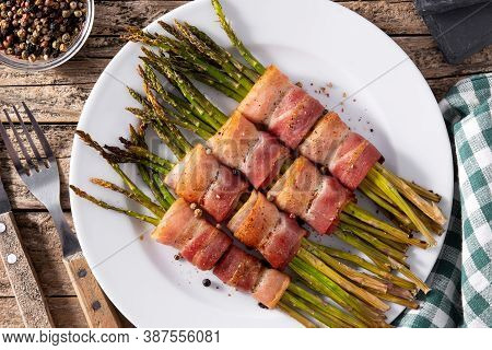 Green Asparagus Wrapped With Bacon On Wooden Table.top View