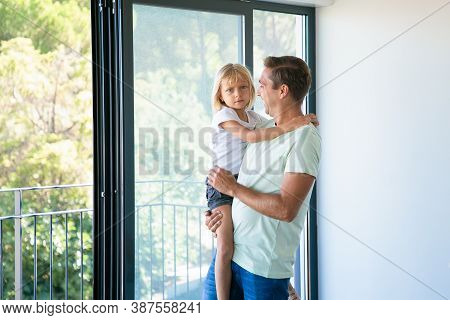Cheerful Father Holding Cute Daughter, Looking At Her And Smiling. Lovely Blonde Girl Looking At Cam
