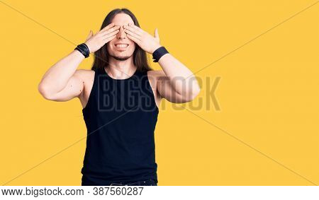 Young adult man with long hair wearing goth style with black clothes covering eyes with hands smiling cheerful and funny. blind concept.