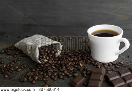 Coffee Beans Scattered From A Linen Bag On A Wooden Table. Cup Of Coffee And Bar Of Dark Chocolate.