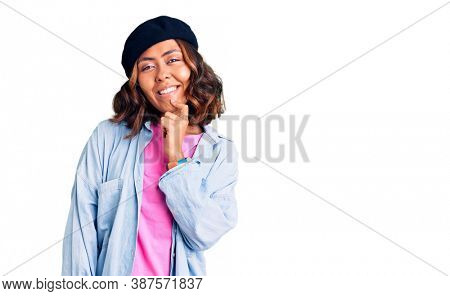 Young beautiful mixed race woman wearing french look with beret looking confident at the camera with smile with crossed arms and hand raised on chin. thinking positive.