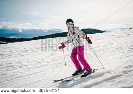 Happy Woman In Glasses Go Skiing On Skis On Snow In Carpathian Mountains. On Background Of Forest An