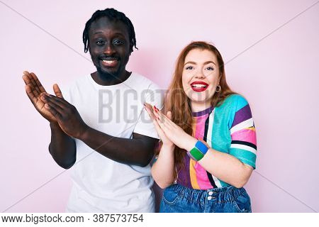 Interracial couple wearing casual clothes clapping and applauding happy and joyful, smiling proud hands together