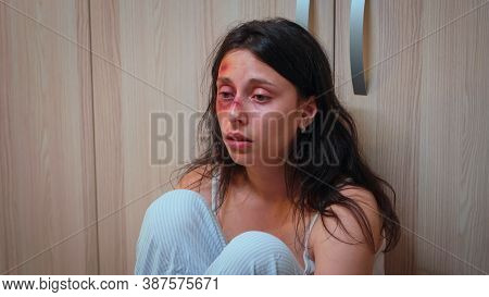 Beaten Woman, Victim Of Domestic Violence Sitting On The Floor. Alcoholic Aggressive Husband Abusing