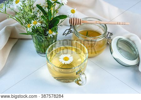 Transparent Cup Of Hot Chamomile Tea And Honey. Concept Of A Healthy Soothing Herbal Drink After A H
