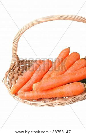 organic carrots in a straw basket isolated on white