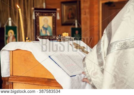 A Priest Holds A Book For Reading Prayers During The Rite Of Baptism In The Orthodox Church.