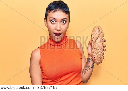 Young woman holding wholemeal bread scared and amazed with open mouth for surprise, disbelief face