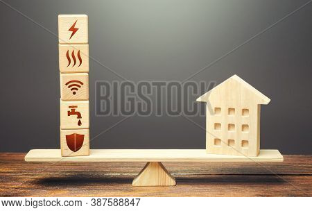 House And Blocks With Utilities Public Service Symbols On Scales. Home Is Too Big And Its Maintenanc
