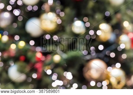 Abstract Blurred Christmas Background With Defocused Lights. Christmas Tree Out Of Focus With Glowin