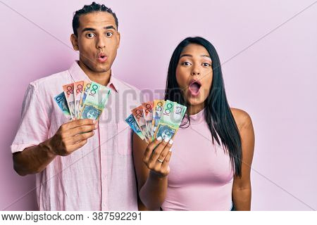 Young latin couple holding australian dollars scared and amazed with open mouth for surprise, disbelief face