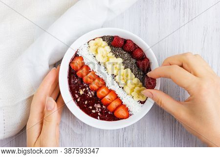 Hand Smoothie Bowl Or Acai Berry Bowl With Chia, Berries, Banana And Coconut Flakes. Woman Hand Puts