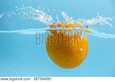 A Ripe Orange Is Falling Into The Clear Water, Forming A Lot Of Splashes. Concept Of Tasty Juicy Fru