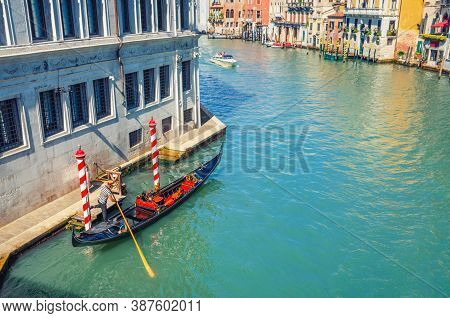 Gondolier On Sailing Gondola Traditional Boat In Water Of Grand Canal Waterway In Venice Historical