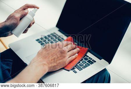 Close Up. Young Man Decontaminating His Laptop
