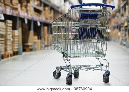 Shopping trolley cart before Rows of shelves with storage boxes in huge warehouse