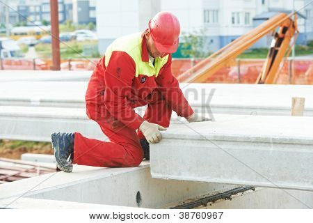 builder worker in safety protective equipment installing concrete floor slab panel at building construction site