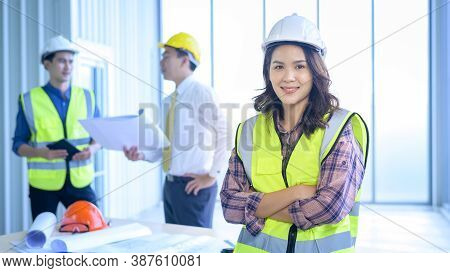 Portrait Of Confident Female Engineer Standing On Frontage While Colleagues Discussing And Meeting O