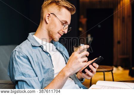 Young Caucasian Man In Glasses Using Mobile Phone And Drink Coffee While Sitting On Chair At Home In