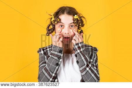 Hairdresser Salon. Girl With Curlers And Hair Clips In Her Hair On Yellow Background. Little Girl Cu