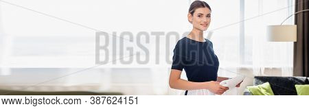 Panoramic Crop Of Chambermaid Holding Clean Towel And Looking At Camera In Hotel Room