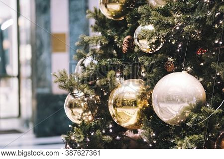 Festive Outdoor Decorative Christmas Lights Background. Christmas Tree Branch Decorated With Baubles