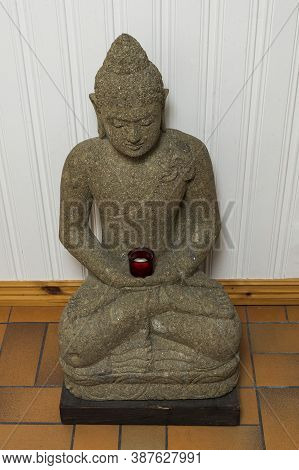 Close Up View Of Grey Buddah Figure On White Wall Background.