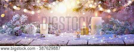 Christmas Decorations With Candles On a Snowy Background
