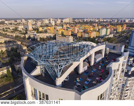 Kyiv, Ukraine - September 2020: Group Of Adults Peoples Doing Yoga Outdoors On The Roof Of The High
