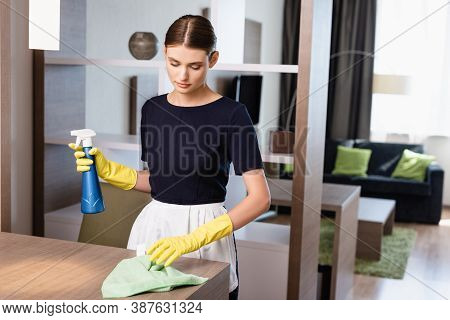 Chambermaid In Apron And Rubber Gloves Spray Bottle And Rag While Cleaning Wooden Surface In Hotel R