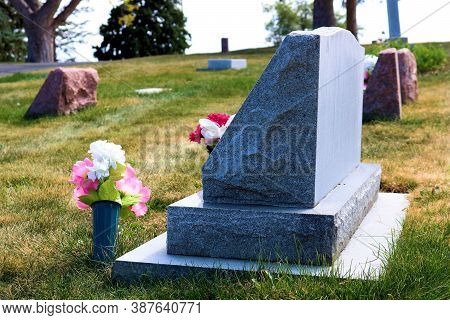Fresh Vases Of Flowers Besides A Vintage Headstone Surrounded By Other Historic Headstones At Grave