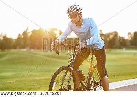 Professional Road Bicycle Racer In Sportswear And Protective Helmet Standing On The Road At Sunset,