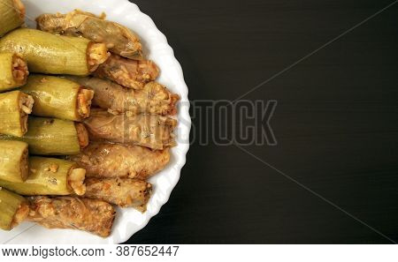 Traditional Stuffed Squash And Cabbage Rolls On White Plate On Dark Wooden Background With Copy Spac