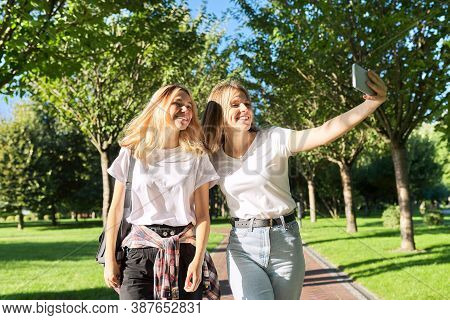 Two Happy Teenage Girls Looking At Webcam Of Smartphone, Girls Take Selfie Photo, Talk Online With F