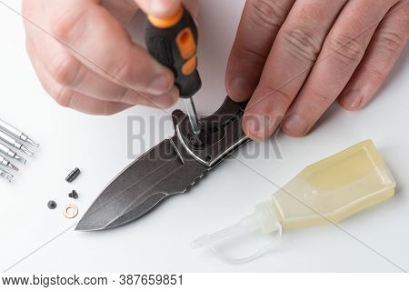 Close-up On Repairmans Hands Assembling The Parts Of A Pocket Knife