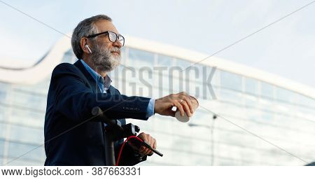 Senior Man In Glasses And Headphones Standing At Bike On Street, Talking And Drinking Coffee To-go.