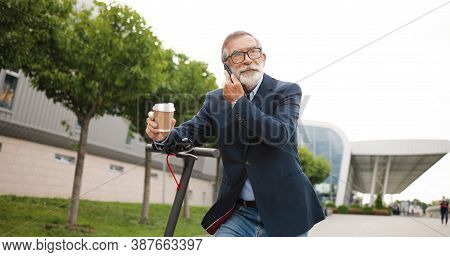 Senior Man In Eyeglasses Standing At Electric Scooter In Town, Drinking Coffee To-go And Talking On