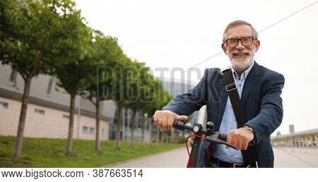 Portrait Shot Of Caucasian Old Man With Gray Hair And In Glasses Sitting On Bike And Looking At Came