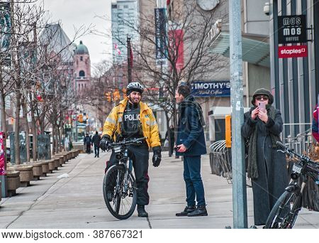 Toronto, Canada - 01 04 2020: Toronto Police Bicycle Patrol Officer Talking With A Man On The Univer
