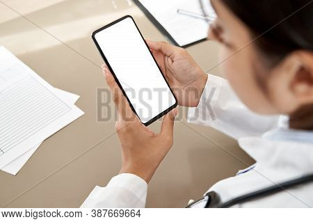 Indian Female Doctor Holding In Hands Using Cell Phone App Mock Up White Screen, Over Shoulder Close