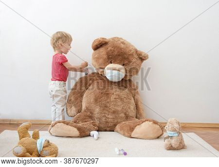 Cute Little Child Playing With His Sick Teddy Bears Wearing Medical Mask Against Viruses. Role Playi