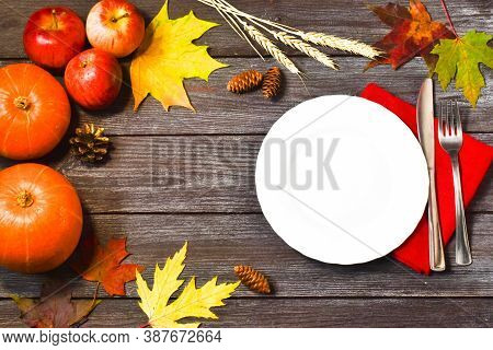 Thanksgiving Dinner. Thanksgiving Day. Autumn Leaves With White Empty Plate, Red Napkin And Cutlery