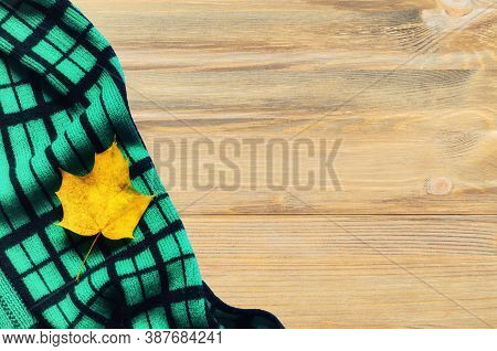 Fall background - dry fall maple leaf and green scarf on the wooden background, free space for text. Fall composition, fall concept, fall rustic background